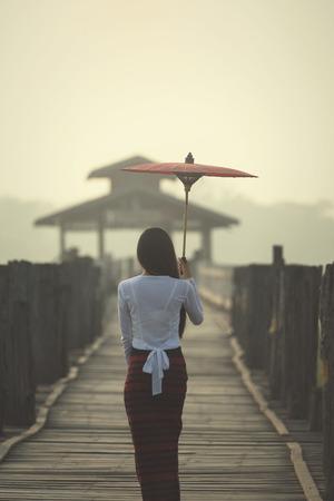 Alone woman walking alone on a bridge