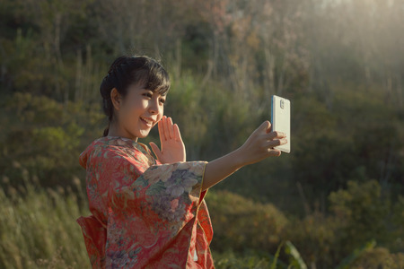 close your eyes: Beautiful smile selfie with smartphone in Kimono traditional japanese dress on the sakura garden.