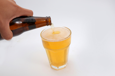 pouring beer: Hand pouring beer isolated on white background