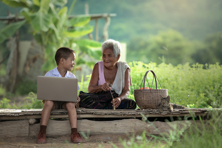 A boy and grandmother with a laptop at cottage Standard-Bild