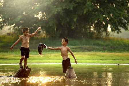 Two boys fishermen were caught fishing in a small lake.