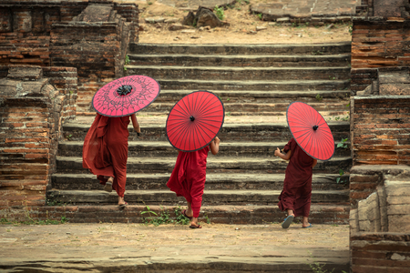 Myanmar The backside three novice walking on the Mingun pagoda and holding red umbrella in Mandalay,Myanmar.