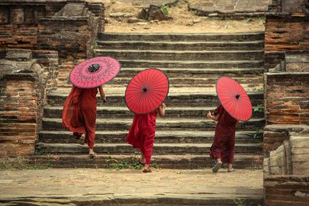 Myanmar El novato de la parte trasera tres en la pagoda de Mingun y sosteniendo el paraguas rojo en Mandalay, Myanmar. Foto de archivo - 75529911