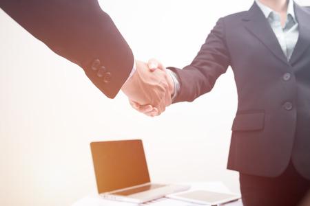 Accordo di stretta di mano di business partner uomo e donna in ufficio moderno avvio del business. Archivio Fotografico - 86579634