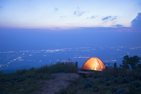 The Camping tent on the hill and Views of the city below before  sunrise at Phu Thap Boek Phetchabun Thailand . 写真素材