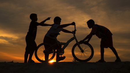 Silhouette The boys joyful with a bicycle on the hill  at sunset and the helping together.