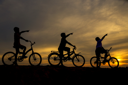 Three boys cycling along the front, pointing to a black silhouette. 写真素材