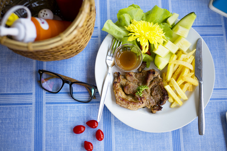 Pork steak in French fries and melon
