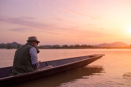 Young man traveling by boat on sunrise hour at Mekong river 写真素材