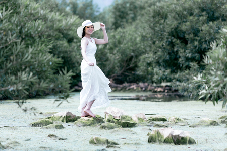 beautiful young lady wearing white dress in motion vintage style on the forest of nature. 写真素材