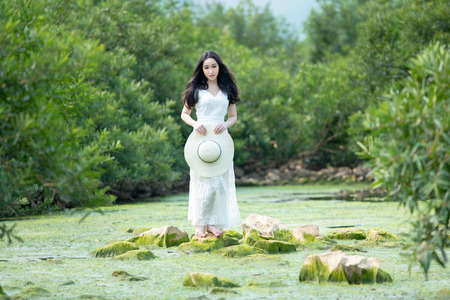 beautiful young lady wearing white dress standing on the stone vintage style on the forest of nature.