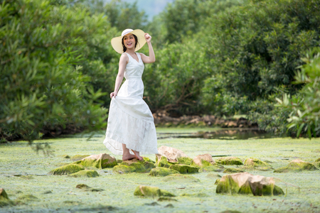 Asian beautiful women wearing white dress in the forest on the creek with sea weed and standing on the stone.