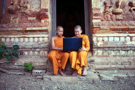 Education of Novice monk Buddhism using laptop learning with friends sitting in the buddhist church at Nong Khai Thailand.