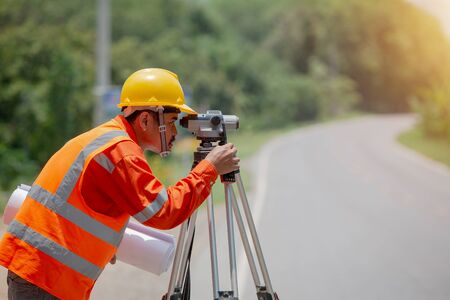 Surveyor marking road construction and land