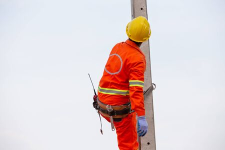 Uniformed electricians working on high-voltage electricity poles with safety equipment.
