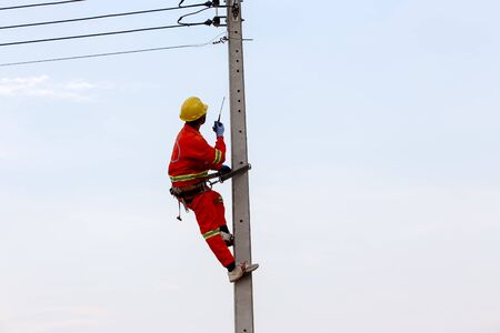 Uniformed electricians work on high-rise electricity poles along with safety equipment and radio communication.