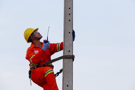 Electricians work on high-voltage electricity poles, along with safety equipment and radio communication.