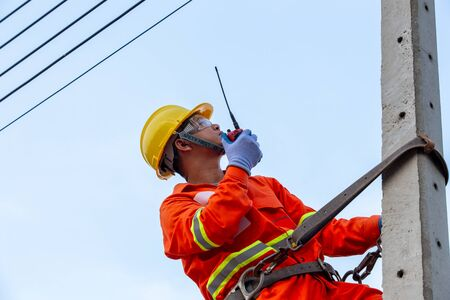 Uniformed electricians work on high-rise electricity poles along with safety equipment and using radio to control their work. Stock fotó
