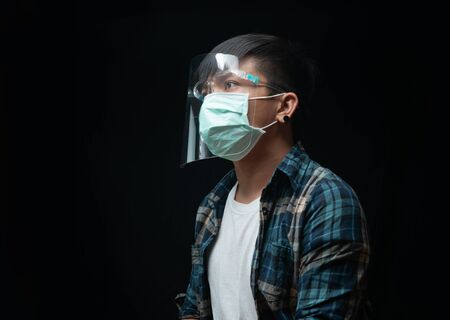 Hopeful man wear a face shield and mask for outbreak Coronavirus or Covid-19, New normal concept