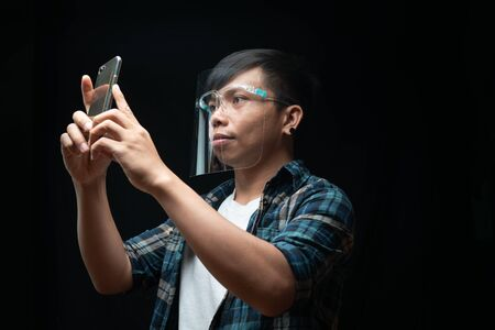 Man wears a face shield using smartphone take photo on the black isolate background