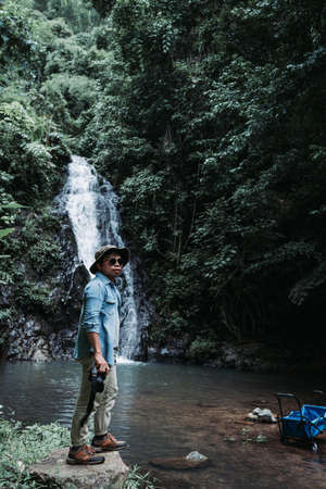 Travel photographer standing at the waterfall Thanthip Sangkhom, Nong Khai Thailand.