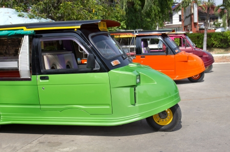 Tuk tuks lined up in a side ally in Thailand