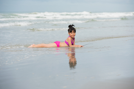 Little children girl black hair with pink, purple swimsuit running playing with sand on a beach and wave sea Standard-Bild