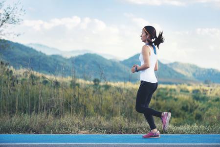 Asiatische junge Fitnessfrau mit Smartwatch im weißen schwarzen Schuh der schwarzen Hose des weißen Anzugs, der an der grünen Rasenfläche der blauen Straßenstraße und am Berghintergrund läuft
