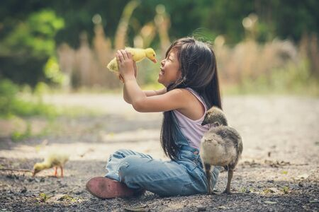 asia children girl holds a duck in hands. girl smile feel happy