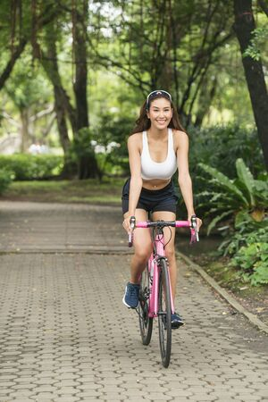 sport asia woman with sunglass on her head in white bra exercise with pink bicycle at park public Stock fotó