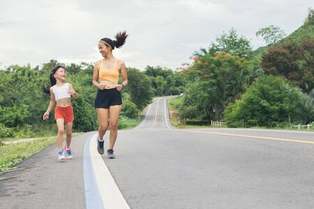 running sporty mother and daughter. woman and child jogging outdoor sports and fitness family. Sport and healthy concept Stock fotó