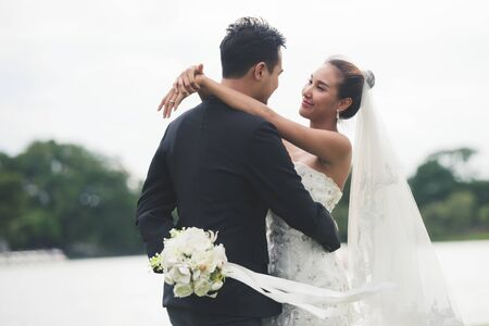 asia bride and groom on the background of river nature. hide flower surprise couple love romantic concept. Stock fotó