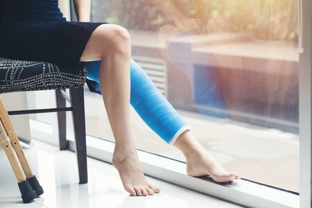 Lesión mujer vestida de negro con férula de pierna azul sentado en una silla y sosteniendo muletas de madera cerca de la ventana en el hospital