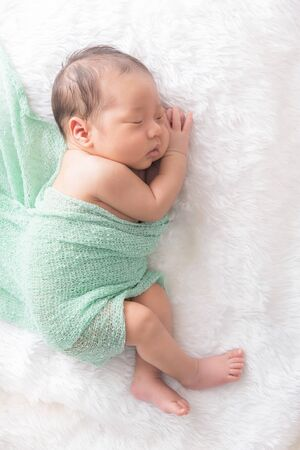 Newborn 7 day old baby boy sleep on  a pink wrap cloth feelgood relaxing Stock fotó