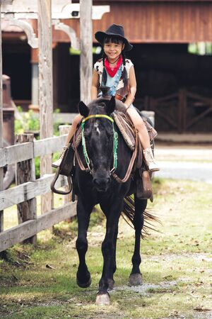 little asia children girl happy smile with hat is riding a black horse