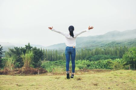 cheering asia woman open arms at mountain peak winter time ratchaburi, thailand