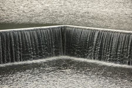 Small dam with water flowing rapids. Seen as lines and patterns with foam Фото со стока