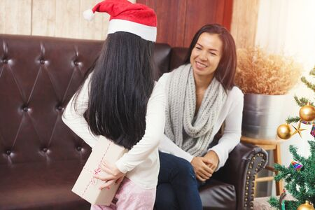Little asia girl in rec santa cap hiding gift box for mom behind her back indoors near cristmas tree. merry cristmas and happy new year concept.