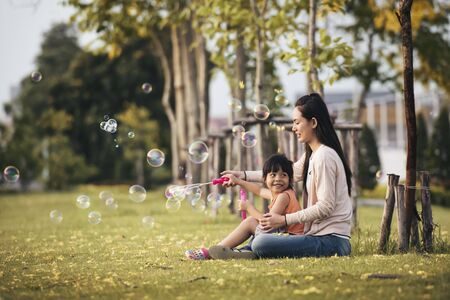 Happy Asian mother and daughter blowing bubbles in park outdoors spending time together.