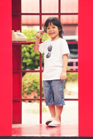 children asia girl smile standing in a red phone booth, look at camera Stock fotó