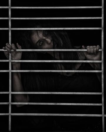Horror Scene of a Possessed Woman black long hair ghost halloween in dark cage pound room Stock fotó