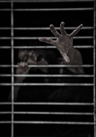 Horror Scene of a Possessed Woman black long hair ghost halloween in dark cage pound room Stock Photo
