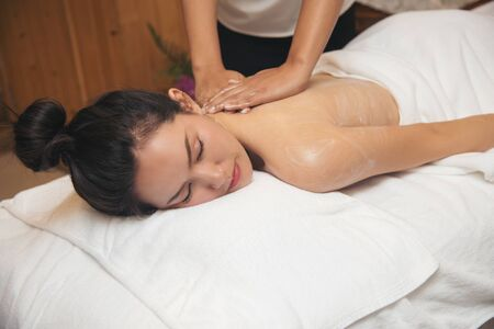 Beautiful young woman getting spa massage salon on white bed.