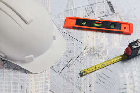 image of white construction helmet with measuring level and site plan Stock fotó