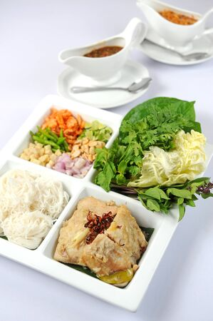 A big assortment of Thai foods and appetizers presented beautifully with fancy garnish. photo
