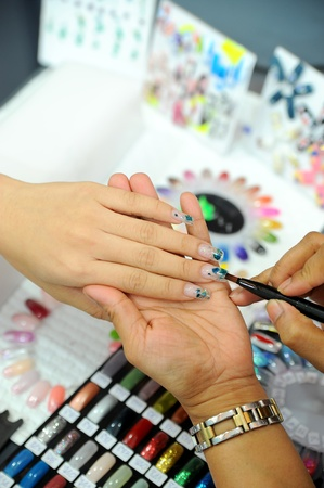 french manicure sexy woman: picture of female hands putting a varnish on nails Stock Photo
