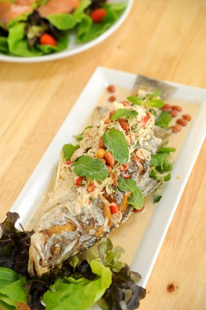 Herb salad with deep fried fish photo