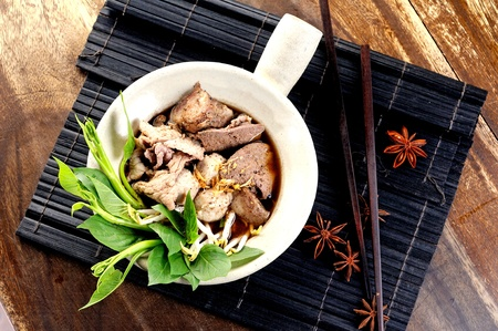 overhead: bowl of pungent thai pork noodle soup served with fresh sweet basil and beansprouts Stock Photo