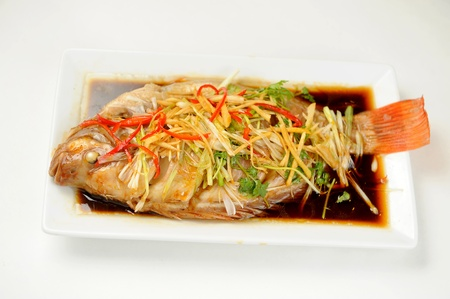 ginger root: Chinese style marinated steamed fish with onion Stock Photo