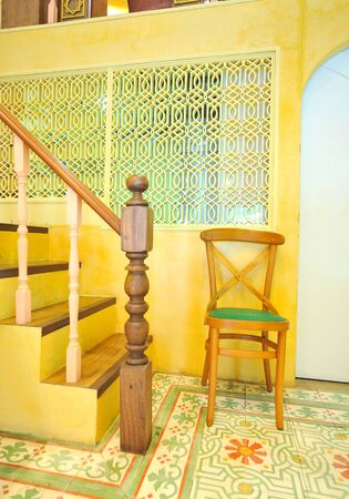 metall lamp: wood chair - yellow background Stock Photo